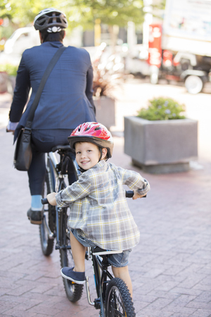 Portrait smiling boy riding tandem bicycle with businessman father