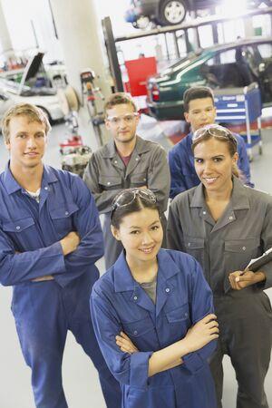 vocational high school: Portrait smiling mechanics in auto repair shop