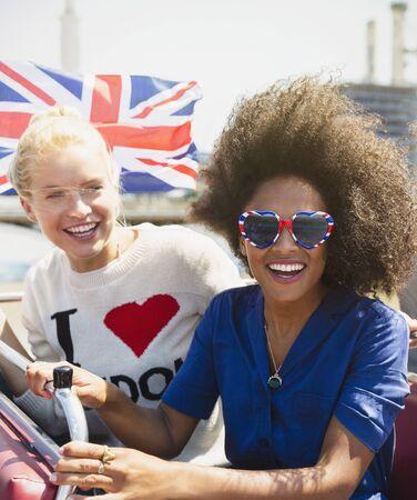 doubledecker: Portrait enthusiastic friends with British flag riding double-decker bus