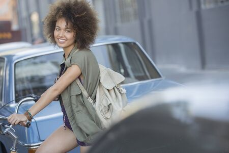 Portrait smiling woman with afro on bicycle in urban street LANG_EVOIMAGES
