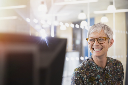 silver surfer: Enthusiastic senior businesswoman looking away in office