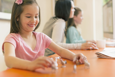 Smiling girl playing with miniature toy animals LANG_EVOIMAGES