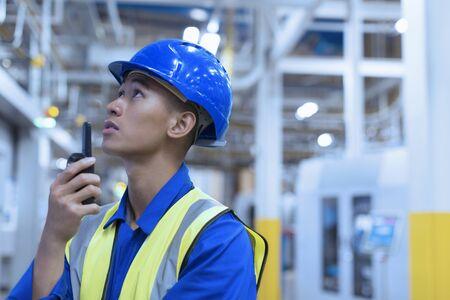 vietnamese ethnicity: Worker in hard-hat using walkie-talkie in factory LANG_EVOIMAGES