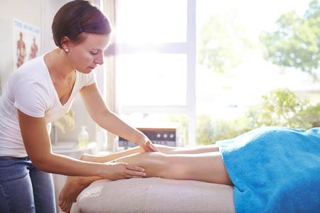 Physical therapist massaging woman's leg
