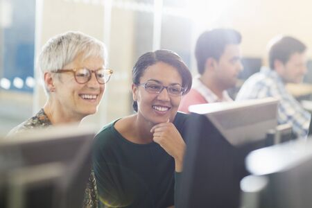 study group: Smiling women at computer in adult education classroom
