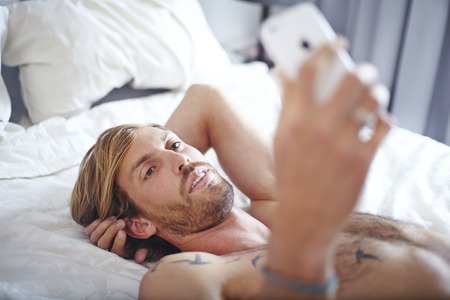 arms behind head: Man with bare chest laying on bed texting with cell phone