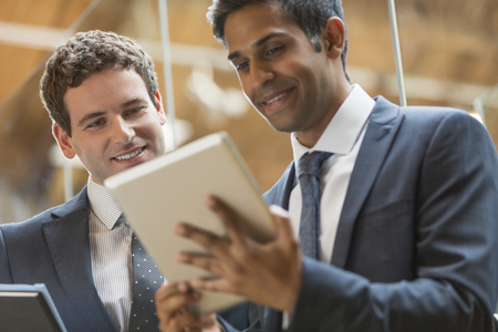 smile close up: Businessmen working with digital tablet in office LANG_EVOIMAGES
