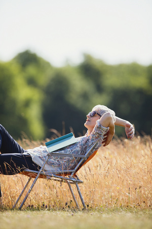 Carefree senior woman relaxing with book in sunny field