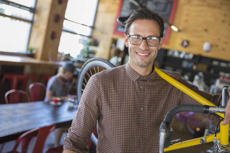 Portrait smiling man with eyeglasses carrying bicycle in cafe