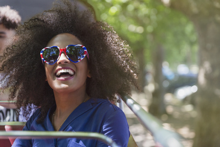 Enthusiastic woman with afro wearing heart-shape glasses