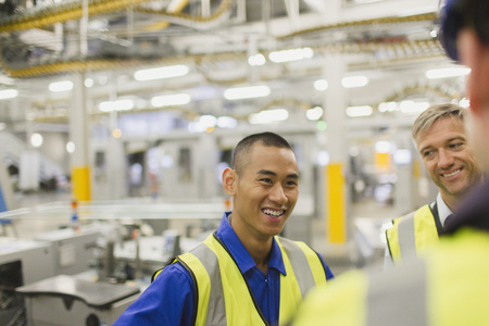 vietnamese ethnicity: Workers in reflective clothing talking in factory