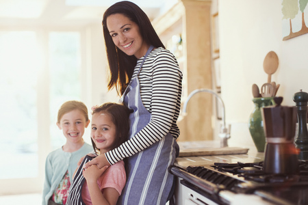 Portrait smiling mother and daughters in kitchen