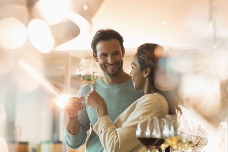 Couple wine tasting in sunny winery tasting room