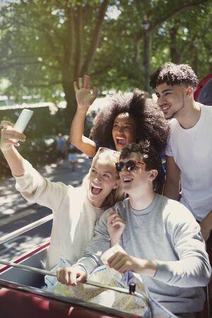 doubledecker: Enthusiastic friends taking selfie on double-decker bus LANG_EVOIMAGES