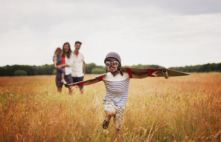 aviators: Playful boy with wings in aviator's cap and flying goggles in field LANG_EVOIMAGES