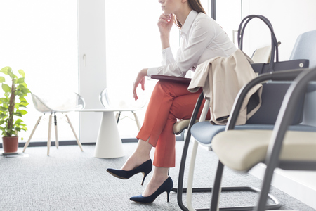 Businesswoman waiting with legs crossed in lobby LANG_EVOIMAGES