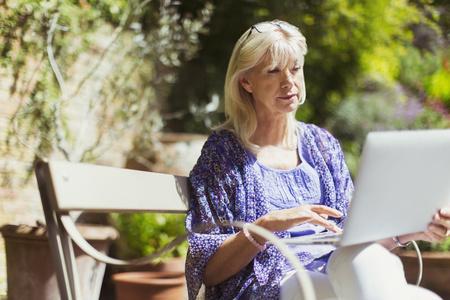 silver surfer: Senior woman using laptop on sunny garden bench LANG_EVOIMAGES