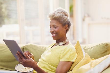 silver surfer: Mature women using digital tablet eating popcorn on sofa