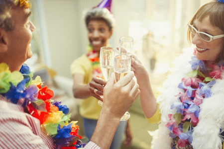leis: Playful mature friends in feather boas and leis toasting champagne flutes