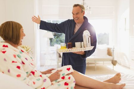 Enthusiastic mature man serving breakfast to wife in bed