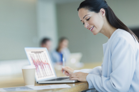 Smiling businesswoman working at laptop with coffee in conference room