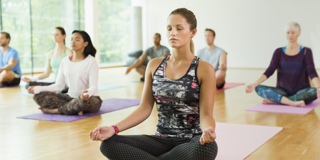 gyan: Serene woman in lotus position with eyes closed in yoga class