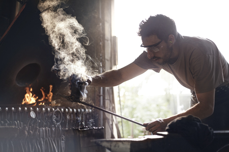 forge: Blacksmith shaping steaming wrought iron in forge