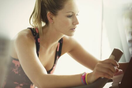waist down: Focused woman using exercise bike at gym