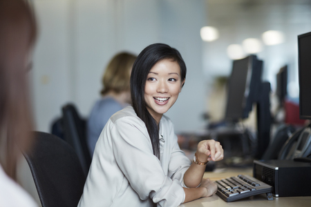 technology: Smiling businesswoman talking to colleague in office LANG_EVOIMAGES