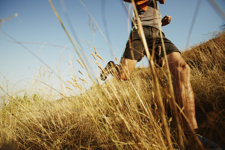 Man running through tall grass on sunny trail LANG_EVOIMAGES