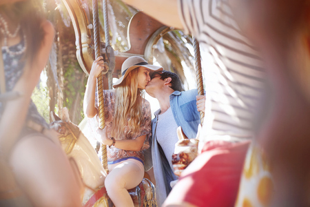 Young couple kissing on carousel at amusement park