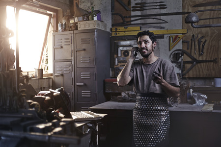forge: Blacksmith talking on cell phone in forge