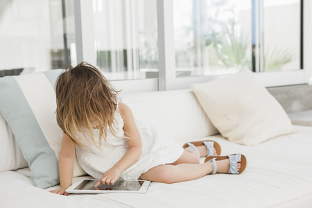 electronic book: Toddler girl using digital tablet on sofa