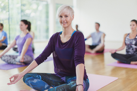 gyan: Portrait smiling woman sitting in lotus position in yoga class