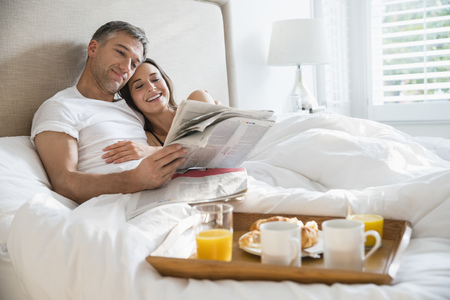 mid morning: Smiling couple reading newspaper enjoying breakfast in bed LANG_EVOIMAGES