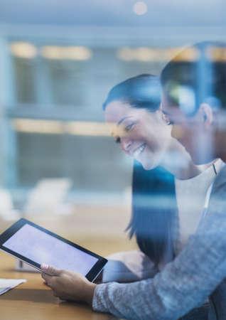 sit down: Sonriendo empresarias con tableta digital en la oficina