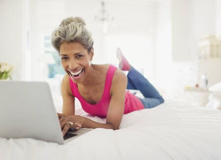 silver surfer: Portrait laughing mature woman using laptop on bed LANG_EVOIMAGES