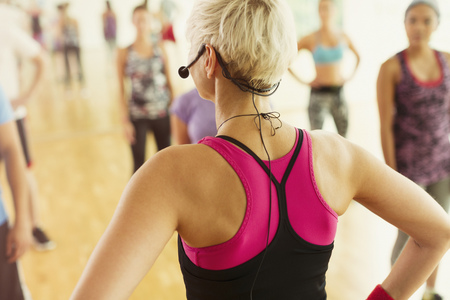 Rear view fitness instructor with headset leading aerobics class