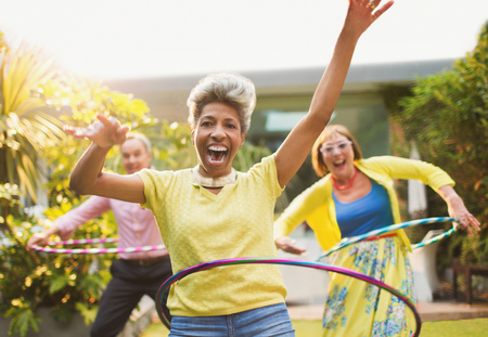 Portrait playful mature adults spinning with plastic hoops in garden LANG_EVOIMAGES