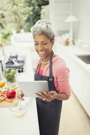 Smiling mature woman with digital tablet cooking in kitchen LANG_EVOIMAGES