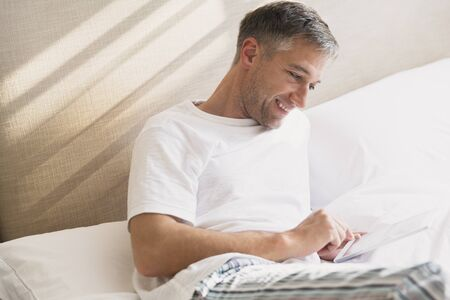 electronic book: Smiling man using digital tablet in bed