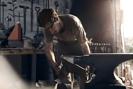 forge: Blacksmith working at anvil in forge LANG_EVOIMAGES