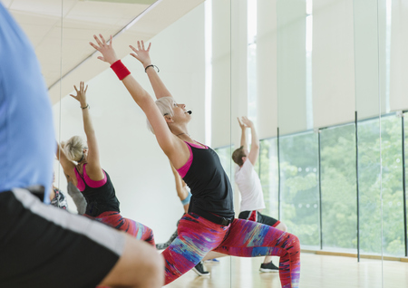 Fitness instructor leading aerobics class in high lunge LANG_EVOIMAGES