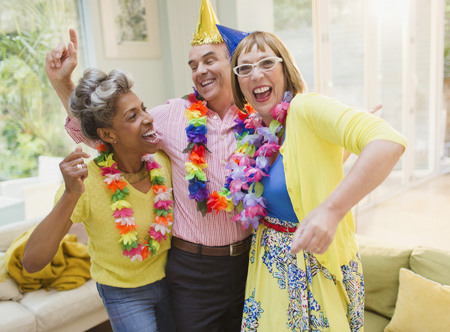 leis: Playful mature adults dancing with leis in living room