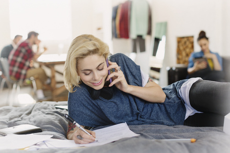 Female college student studying and talking on cell phone on bed LANG_EVOIMAGES