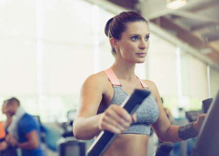 eliptica: Focused woman exercising on elliptical trainer in gym