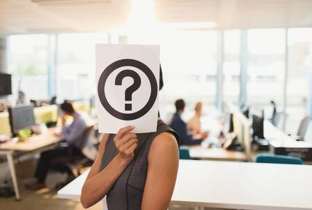 Portrait of businesswoman holding question mark printout over her face in office