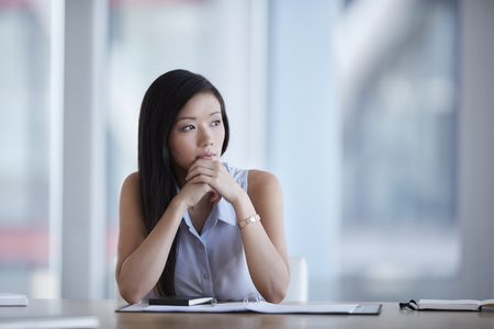 Pensive businesswoman looking away in conference room LANG_EVOIMAGES