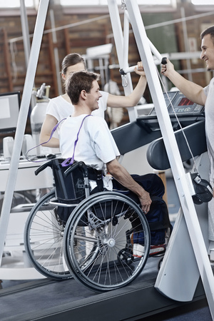 Physical therapists guiding man in wheelchair on treadmill  LANG_EVOIMAGES