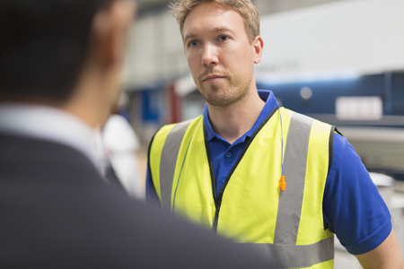 Serious worker listening to manager in steel factory